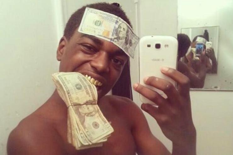 Kodak Black takes a selfie with dollars bills stuck in his mouth and on his forehead