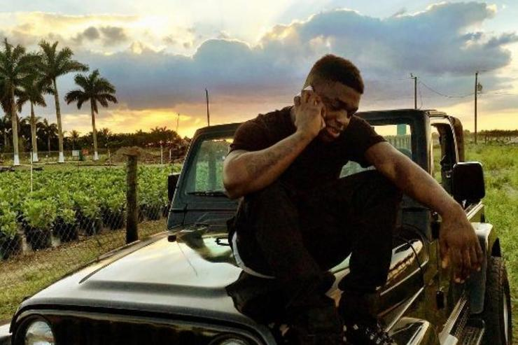 Kodak Black makes a cellphone call sitting on the hood of his jeep.