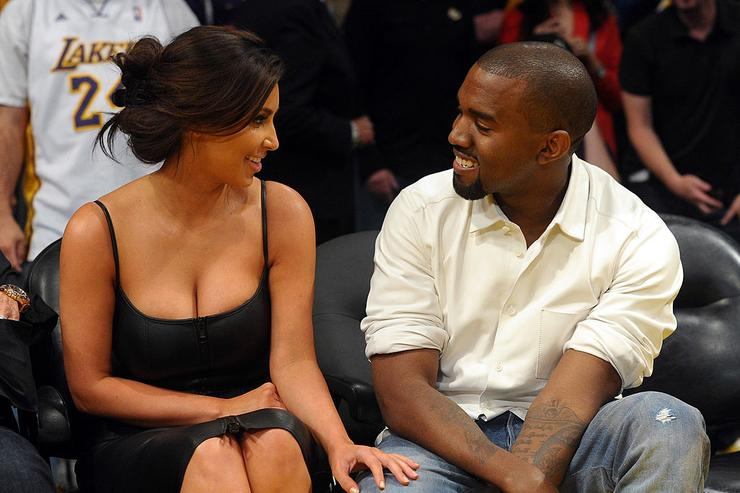 Kim Kardashian and Kanye West talk from their courtside seats before the Los Angeles Lakers take on the Denver Nuggets in Game Seven of the Western Conference Quarterfinals in the 2012 NBA Playoffs on May 12, 2012 at Staples Center in Los Angeles, California.